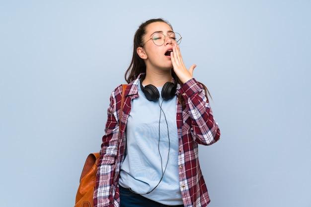 Nastolatek studencka dziewczyna nad odosobnioną błękit ścianą ziewa i zakrywa szeroko otwarte usta ręką Premium Zdjęcia