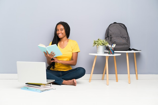 Nastolatek studencka dziewczyna siedzi na podłodze i czyta książkę Premium Zdjęcia