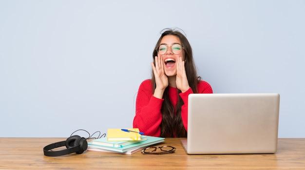 Nastolatek studencka dziewczyna studiuje w stole krzyczy coś i ogłasza Premium Zdjęcia