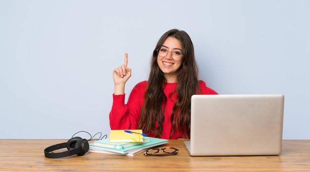 Nastolatek studencka dziewczyna studiuje w stole pokazuje palec w znaku best i podnosi Premium Zdjęcia