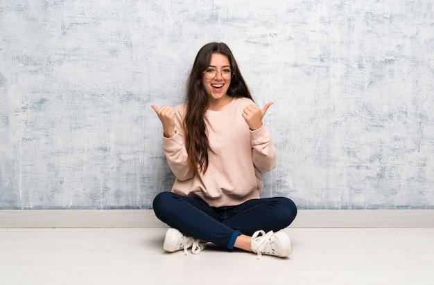 Nastolatek studencka dziewczyna studiuje w stole z aprobata gestem i ono uśmiecha się Premium Zdjęcia
