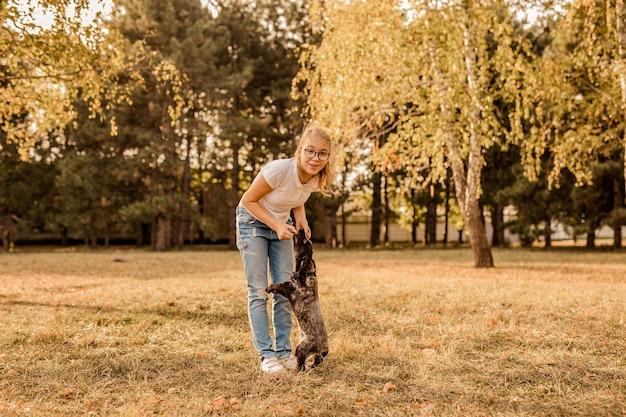 Nastolatka Blondynka W Dużych Okularach, śmiejąc Się I Bawiąc Się Z Małym Szczeniakiem Spanielem W Ciepłym Parku. Premium Zdjęcia