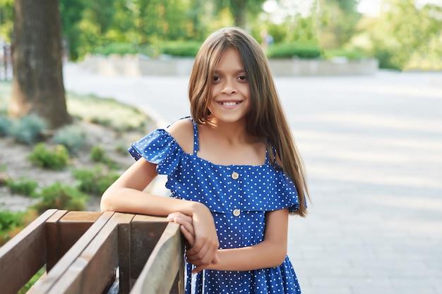 Nastolatka dziewczyny w niebieskiej sukience spacery w parku lato o zachodzie słońca Premium Zdjęcia