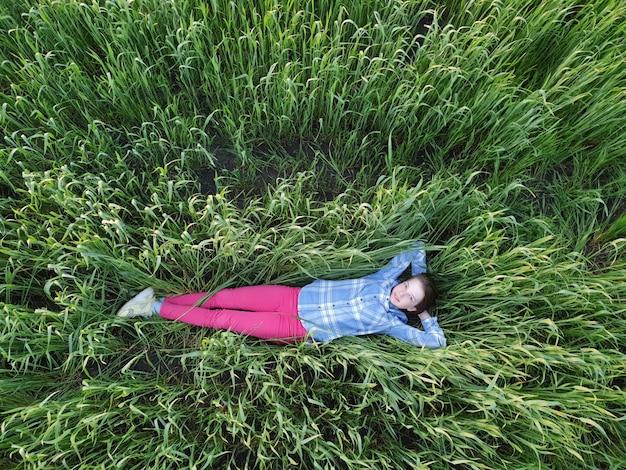 Nastolatka Leży W Zielonej Trawie O Zachodzie Słońca, Widok Z Góry, Spacery I Jedność Z Naturą Premium Zdjęcia