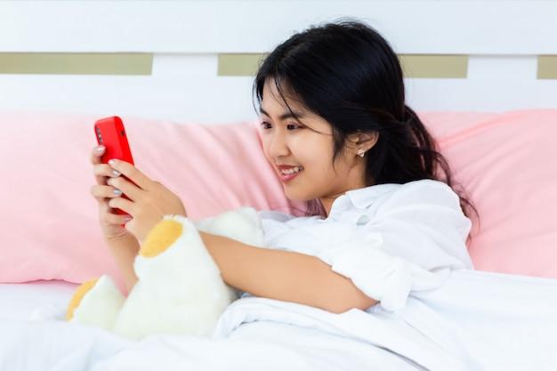 Nastolatka use żeński smartphone na łóżku Darmowe Zdjęcia