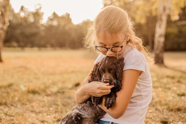 Nastolatka W Okularach, Grając Na Trawie Z Psem, Brązowy Cocker Spaniel Szczeniak, Na Zewnątrz, W Parku. Premium Zdjęcia