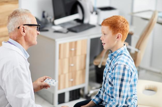 Nastoletni Chłopak Rozmawia Z Lekarzem W Health Check Up Premium Zdjęcia