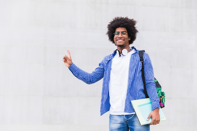 Nastoletni chłopiec trzyma książki w ręce wskazuje jego palec oddolnego przeciw białej betonowej ścianie Darmowe Zdjęcia
