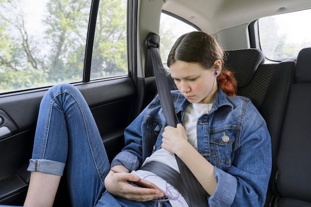 Nastoletni Dziewczyny Obsiadanie W Samochodzie W Tylnym Miejscu Pasażera Z Smartphone I Hełmofonami Premium Zdjęcia