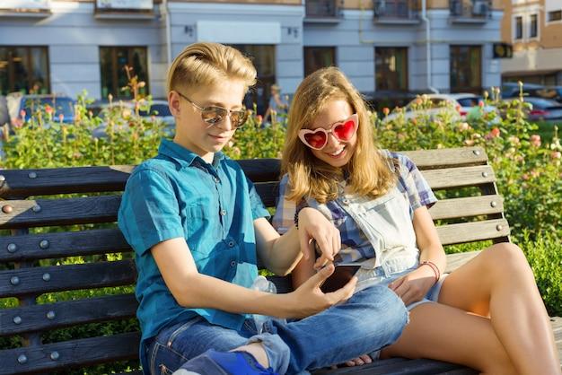 Nastoletni przyjaciele dziewczyna i chłopak siedzi na ławce w mieście Premium Zdjęcia