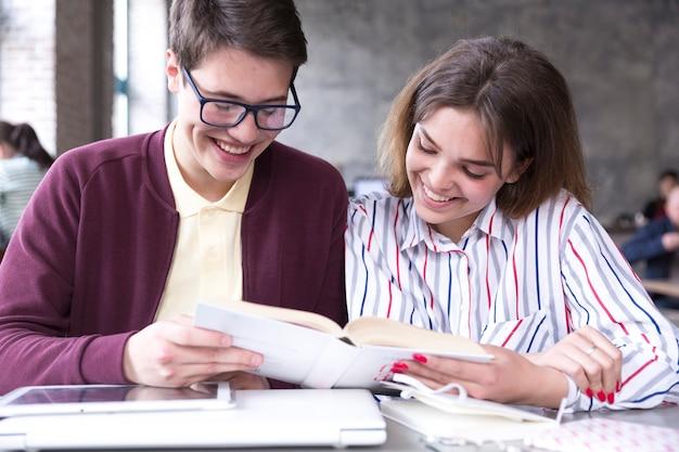 Nastoletni Ucznie Uśmiecha Się I Czyta Książki Przy Stołem Darmowe Zdjęcia
