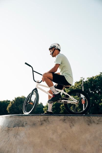 Nastoletnia bmx jeźdza pozycja z jego roweru niskiego kąta widokiem Darmowe Zdjęcia