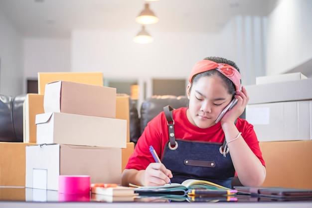 Nastoletnia dziewczyna azjatycka przygotowuje w domu skrzynki dostawcze na potrzeby sprzedaży online. młoda przedsiębiorca lub niezależna dziewczyna rozpoczynają małą firmę, sprzedając coś online. Premium Zdjęcia