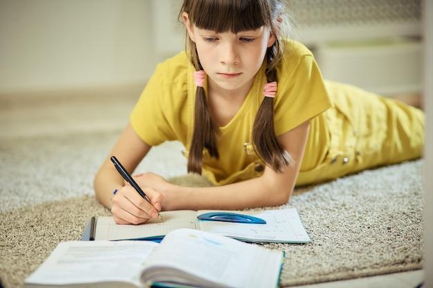 Nastoletnia dziewczyna robi pracie domowej siedzi na dywanie w jej pokoju Premium Zdjęcia