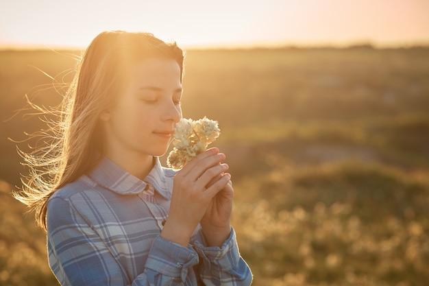 Nastoletnia Dziewczyna W Polu Przy Zmierzchem Z Kwiatami W Jej Rękach. Premium Zdjęcia