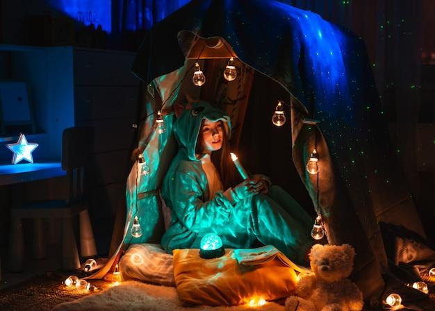Nastoletnia Dziewczyna W Postaci Anime Siedzącej W Domu Namiotu Gry. Sceneria Z Fantastycznym Oświetleniem Wianek Premium Zdjęcia