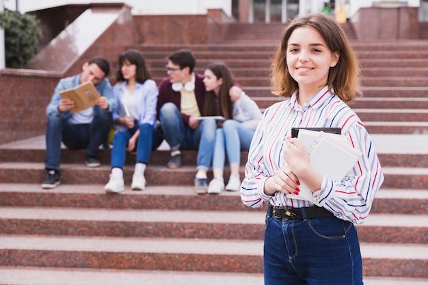 Nastoletniej dziewczyny pozycja i mienie notatnik w rękach Darmowe Zdjęcia