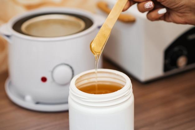 Naturalna pasta z gorącego cukru do depilacji w słoiku i na drewnianej szpatułce w rękach kosmetyczki Premium Zdjęcia