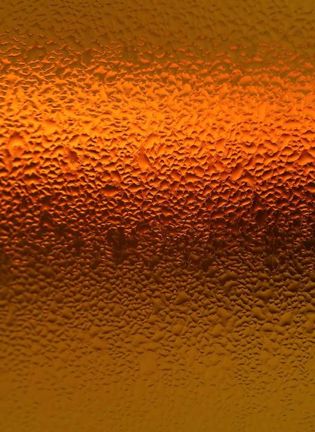 Naturalne kropelki wody na jasny kolor pomarańczowy butelki, pionowe zdjęcie na streszczenie tło z selektywnej ostrości Premium Zdjęcia
