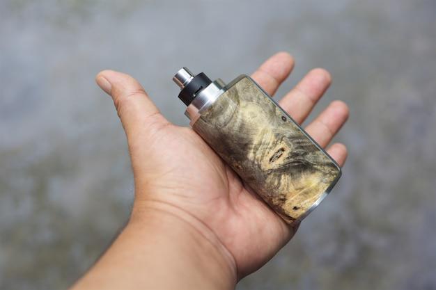 Naturalne Stabilizowane Modowe Pudełka Z Drewna Z Regenerowanym Kapiącym Atomizerem I Pierścieniem Upiększającym W Dłoni, Waporyzator Premium Zdjęcia