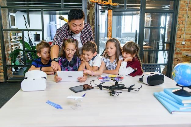 Nauczyciel Azjatycki Pracuje Z Pięcioma Młodymi Uczniami Korzystającymi Z Urządzeń Cyfrowych W Klasie Technologii. Koncepcja Edukacji, Nauki, Rozwoju I Nowoczesnych Technologii. Premium Zdjęcia