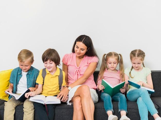 Nauczyciel I Dzieci Siedzą Razem Premium Zdjęcia