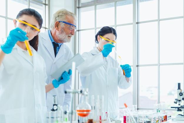 Nauczyciel nauk ścisłych i zespół studentów pracujących z chemikaliami w laboratorium Premium Zdjęcia