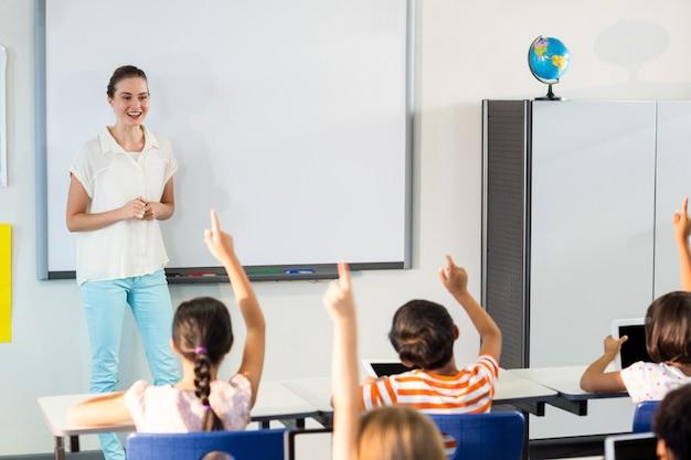 Nauczyciel Patrząc Na Uczniów Podnoszących Ręce Premium Zdjęcia