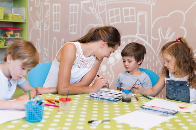 Nauczyciel Pomaga Dziecku Malować Darmowe Zdjęcia
