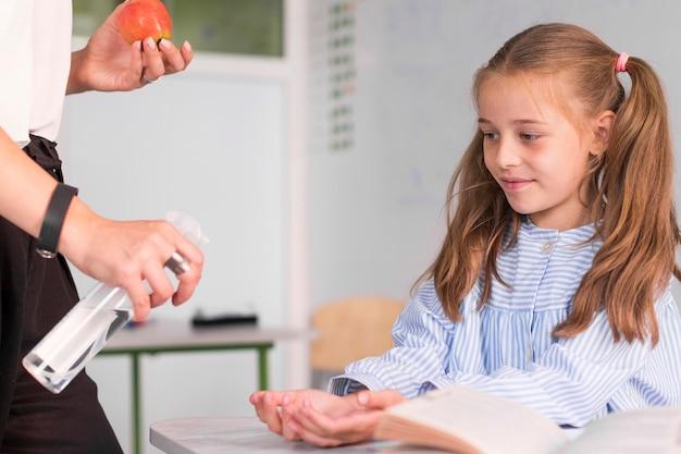 Nauczyciel Pomaga Dziewczynie Dezynfekować Ręce Darmowe Zdjęcia
