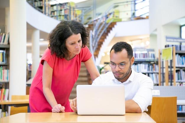 Nauczyciel pomaga uczniowi pracującemu nad projektem Darmowe Zdjęcia