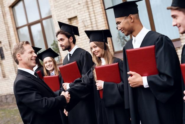 Nauczyciel wręcza studentom dyplomy na dziedzińcu uniwersytetu Premium Zdjęcia