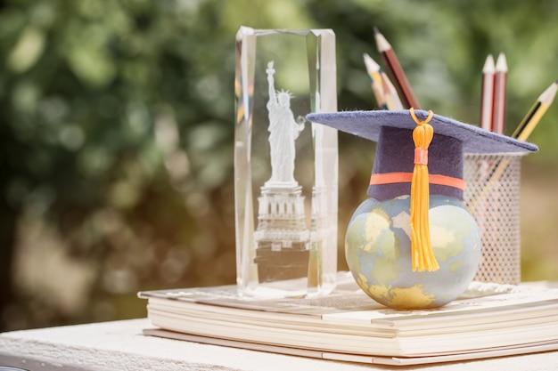 Nauka Międzynarodowa Za Granicą W Ameryce Koncepcja: Czapka Absolwenta Na Mapie Modelu Globu Ziemskiego W Książce Premium Zdjęcia