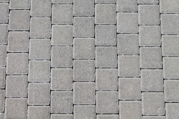 Nawierzchnię Drogi Wykonano Z Naturalnego Kamienia W Postaci Kwadratowych Płytek. Naturalny Wygląd Tekstury Premium Zdjęcia