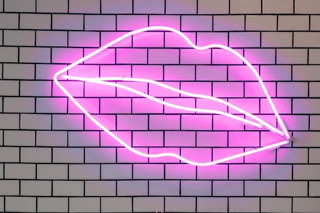 Neony W Kształcie Warg Led świecące Dekoracyjne światła, Dekoracje ścienne. Fioletowe Lampy Fluorescencyjne Na Wyłożonej Kafelkami Białej ścianie Z Cegły. Premium Zdjęcia