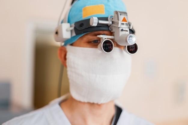 Neurochirurg W Białej Masce, W Specjalnym Ubraniu Medycznym, W Lupach Z Lupą Lornetkową, Jest W Szpitalu. Okulary Chirurgiczne. Wyposażenie Medyczne Premium Zdjęcia