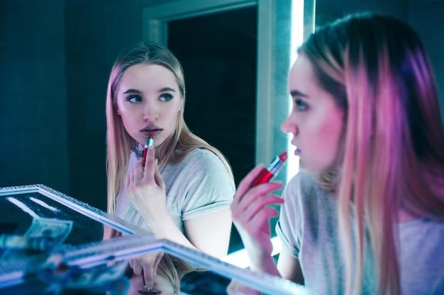 Nie Dla Narkotyków. Portret Młodej Pięknej Kobiety Stosujące Usta Czerwoną Szminką W Pobliżu Linii Kokainy W Nocnym Klubie Toalety. Patrzy W Lustro. Dodatek Do Zdrowego Stylu życia Lub Narkotyków Premium Zdjęcia