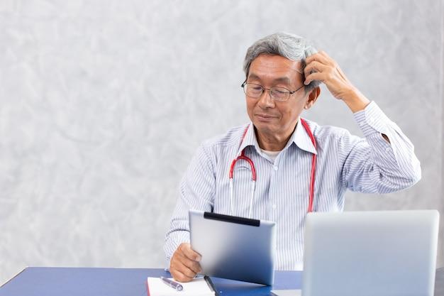 Nie Do Pomyślenia Doktorze, Staruszek Chińczyk Korzystający Z Tabletu Komputerowego, Mylący Się Z Problemem Problemów Zdrowotnych Związanych Z Wirusem Koronowym. Premium Zdjęcia