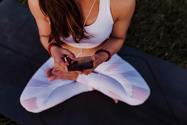 Nie Do Poznania Azjatycka Kobieta Zrelaksowana Po Treningu Jogi Słuchając Muzyki Na Słuchawkach I Telefonie Komórkowym. Premium Zdjęcia