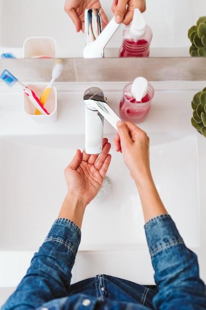 Nie Do Poznania Kobieta Mycie Rąk Na Zlewie Mydłem. Premium Zdjęcia