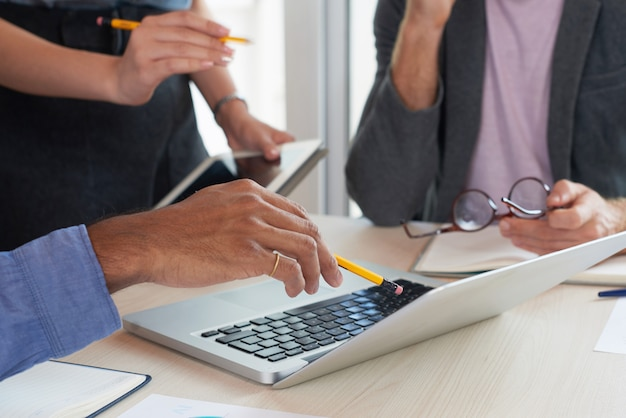 Nie do poznania koledzy, patrząc na ekran laptopa na spotkaniu pracy Darmowe Zdjęcia