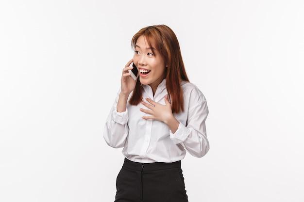 Nie Ma Mowy, Wow. Zaskoczony Zadowolony Szczęśliwy Uśmiechnięta Kobieta Azji Rozmawia Przez Telefon Komórkowy, śmiejąc Się Zdziwiona I Wesoła, Słyszy Wspaniałe Wieści, Trzymając Smartfon Przy Uchu Podczas Rozmowy Premium Zdjęcia