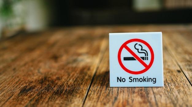 Nie Palić Znak Zakaz Palenia W Miejscach Publicznych Znak Zakazu Palenia Na Drewnianym Stole W Hotelu Premium Zdjęcia