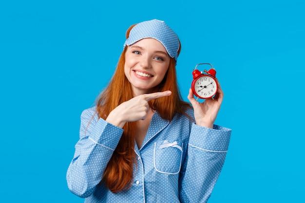 Nie Zapomnij Obudzić Się Na Czas. Wesoła I Urocza Zrelaksowana Kobieca Ruda Kobieta W Piżamie Premium Zdjęcia