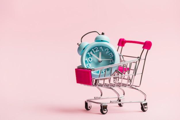 Niebieski budzik w miniaturowym wózku na zakupy Darmowe Zdjęcia