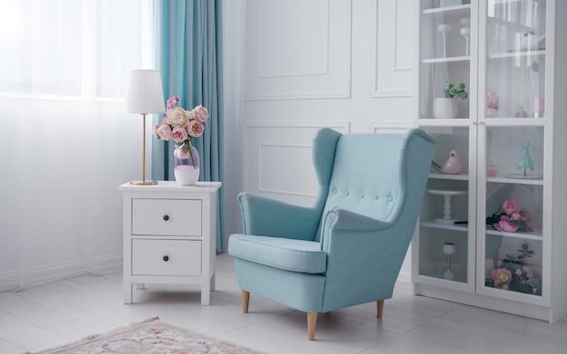 Niebieski Klasyczny Fotel I Biała Szafka Z Szufladami Z Lampą Stołową I Wazonem Na Kwiaty W Białym Pokoju Premium Zdjęcia