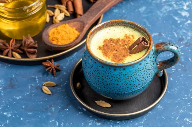 Niebieski Kubek Tradycyjnego Indyjskiego Złotego Mleka Z Kurkumy Z Kardamonem, Anyżem, Miodem I Cynamonem Na Niebiesko. Premium Zdjęcia