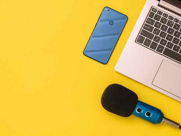 Niebieski Mikrofon Niebieski Smartfon I Laptop Przy żółtym Stole. Pojęcie Organizacji Miejsca Pracy. Sprzęt Do Nagrywania, Komunikacji I Słuchania Muzyki. Premium Zdjęcia