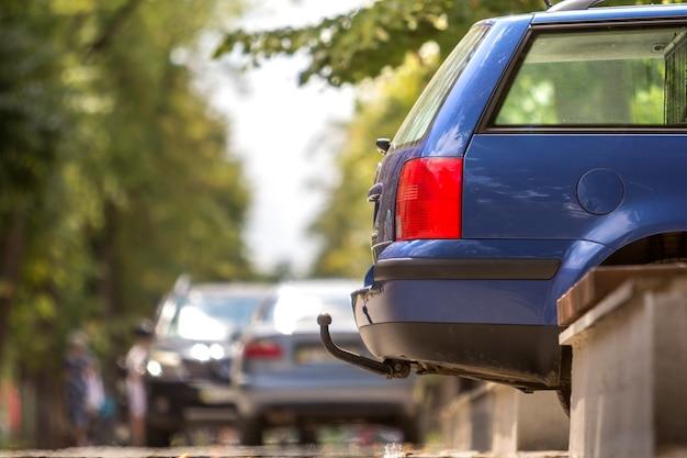 Niebieski Samochód Zaparkowany Na Słonecznej Ulicy, Czerwone światła Stopu, Hak Do Ciągnięcia Przyczepy Premium Zdjęcia