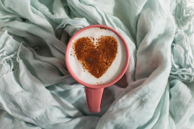 Niebieski szalik, kawa z wzorem serca na stole, dzień dobry to najlepszy początek dnia. jesieni trybowy tło, copyspace. Premium Zdjęcia